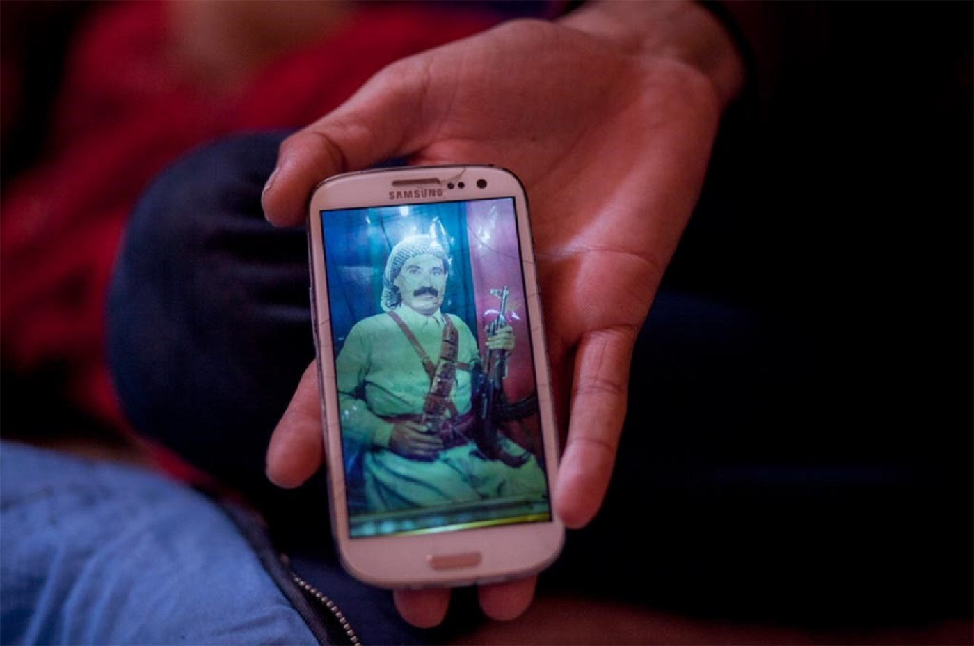 "Baxtyar, a young Kurdish Iraqi refugee who had been a Peshmerga fighter against the IS, shows a photograph of his father (also Peshmerga) on his mobile phone. Refugee camp ""Jungle"", Dunkirk, France."