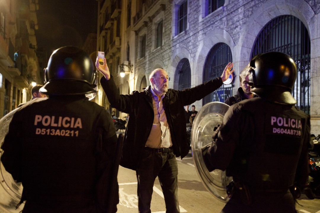 A man trying to pass the police line with his ID in hand. New night of riots in Barcelona. October 26, 2019.