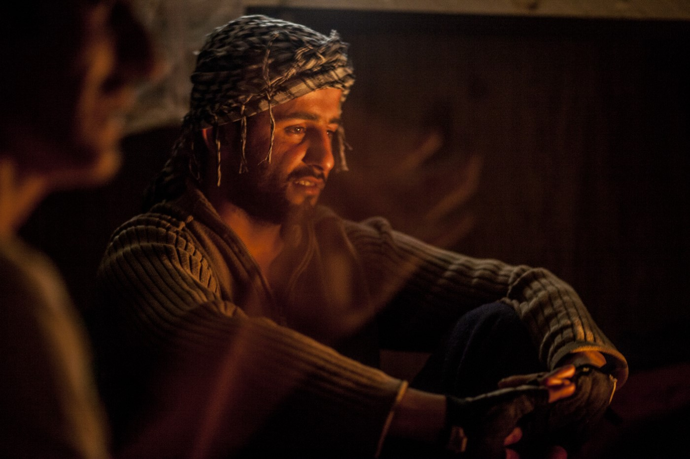 Haval, also an Iraqi Kurdish refugee, listens to the singing of his partner Baxtyar one night in the wooden hut where they sleep.