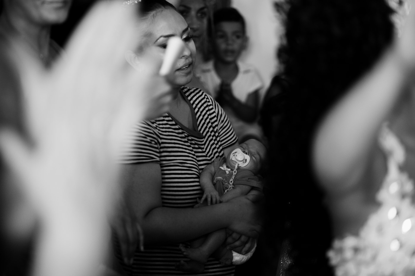 A woman holds her child during the scarf test (yeli).