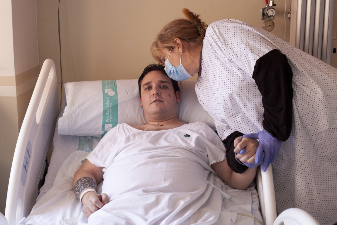 Marc Gil (33 years old) with his mother on the floor of the Taulí hospital after being admitted to the ICU for two months by Covid-19. Marc is one of the longest cases of coronavirus in Sabadell. He had two cardiac arrests and was intubated three times. He stayed all the rooms that had been enabled as an ICU. He is alive by a miracle. Marc is an SEM ambulance technician. He was on the front line from the time the pandemic started until he felt bad. He says that patients died in his arms, with an average of 5 people with Covid-19 who did not even reach the hospital. He, like other colleagues, had one mask per week and had to wash it with bleach. They did not have the necessary EPIS and also, since they were small, they had open areas. That is why he is convinced that he took so much viral load that that he almost died. Now, he is recovering from notable consequences that he tries to recover by doing rehabilitation in the same hospital. He has nervous tics, speech difficulties, impaired movements, taste, smell, and hair loss. June 27, 2020; Sabadell, Barcelona.