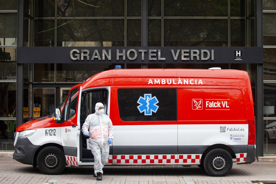An ambulance and a professional protected with PPE in front of the Hotel Verdi where it welcomes patients (39) with covid-19 derived from the Taulí Hospital. Hotels enabled to decongest hospitals. March 30, 2020; Sabadell, Barcelona.