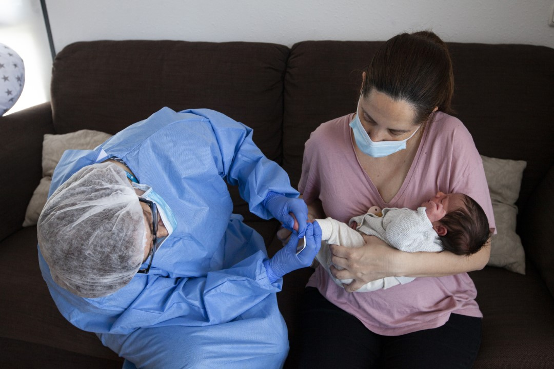 The midwife of the CAP Norte of Sabadell (Barcelona), Concepción Manzano, doing the heel test on Emma at her home. The Covid-19, caused that after the delivery, the return home was immediate, discharging the mothers 12 hours later. April 30, 2020; Sabadell, Barcelona.