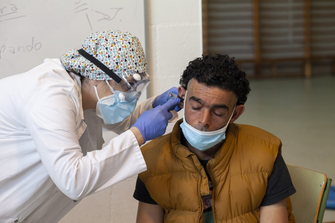 Temporary shelter within a school for the homeless in Sabadell (Barcelona) during confinement and in the middle of the coronavirus pandemic. In the image, Hesham, homeless, with the South CAP doctors treating him for an ear infection. April 28, 2020; Sabadell, Barcelona.