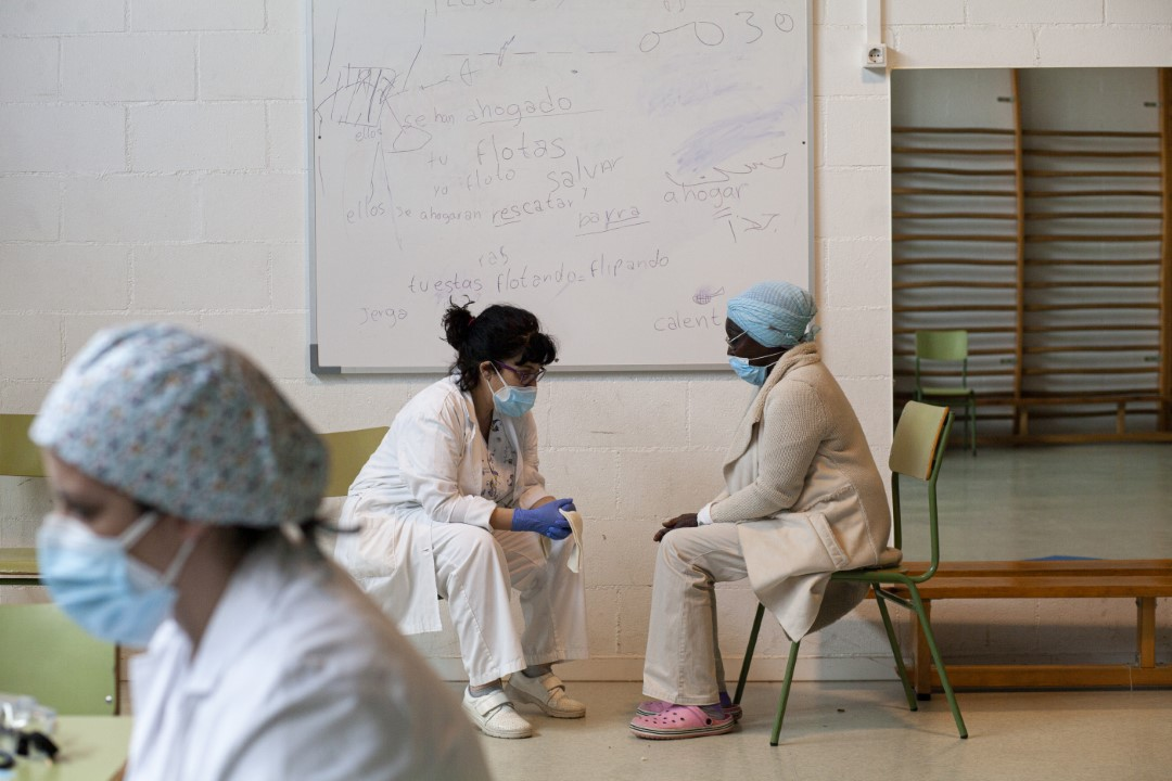 Temporary shelter within a school for the homeless in Sabadell (Barcelona) during confinement and in the middle of the coronavirus pandemic. In the image, Angelina, homeless, with the South CAP doctors. April 28, 2020; Sabadell, Barcelona.