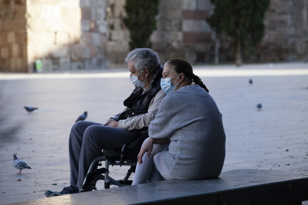A man in a wheelchair and her companion, sitting alone in front of the Cathedral of Barcelona during the time slot of + 70 years, after 7 weeks in lockdown to fight the Covid-19. May 2, 2020. Barcelona.
