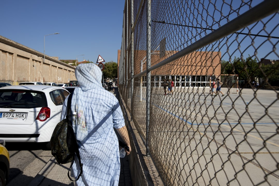 A woman observes the children playing in the courtyard of the Teresa Claramunt school on the first day of the school reopening 6 months later due to Covid-19. September 14, 2020; Sabadell, Barcelona.
